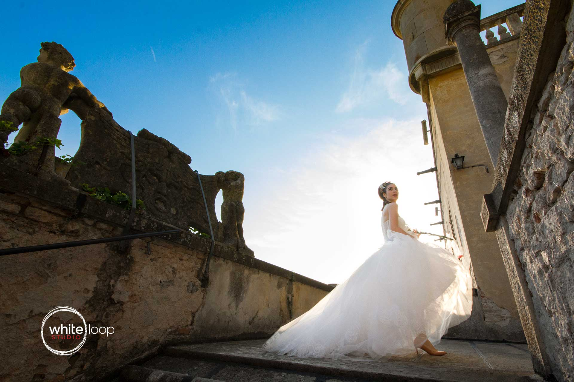 The bride is posing in her wedding dress in the ancient castle of Catajo covering with his beauty the sun.