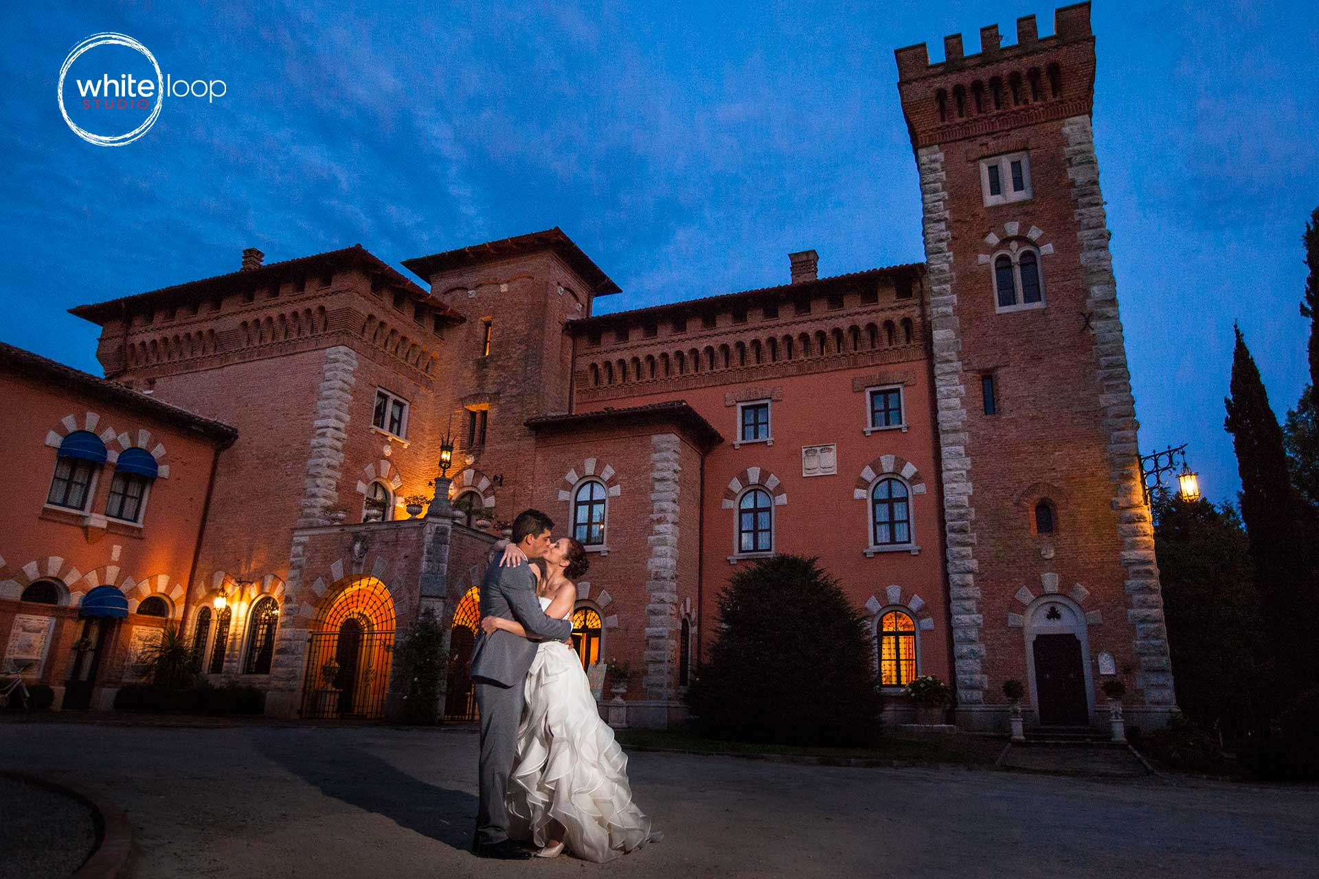 The bride and groom are kissing outside of the castle, while the night time begin.
