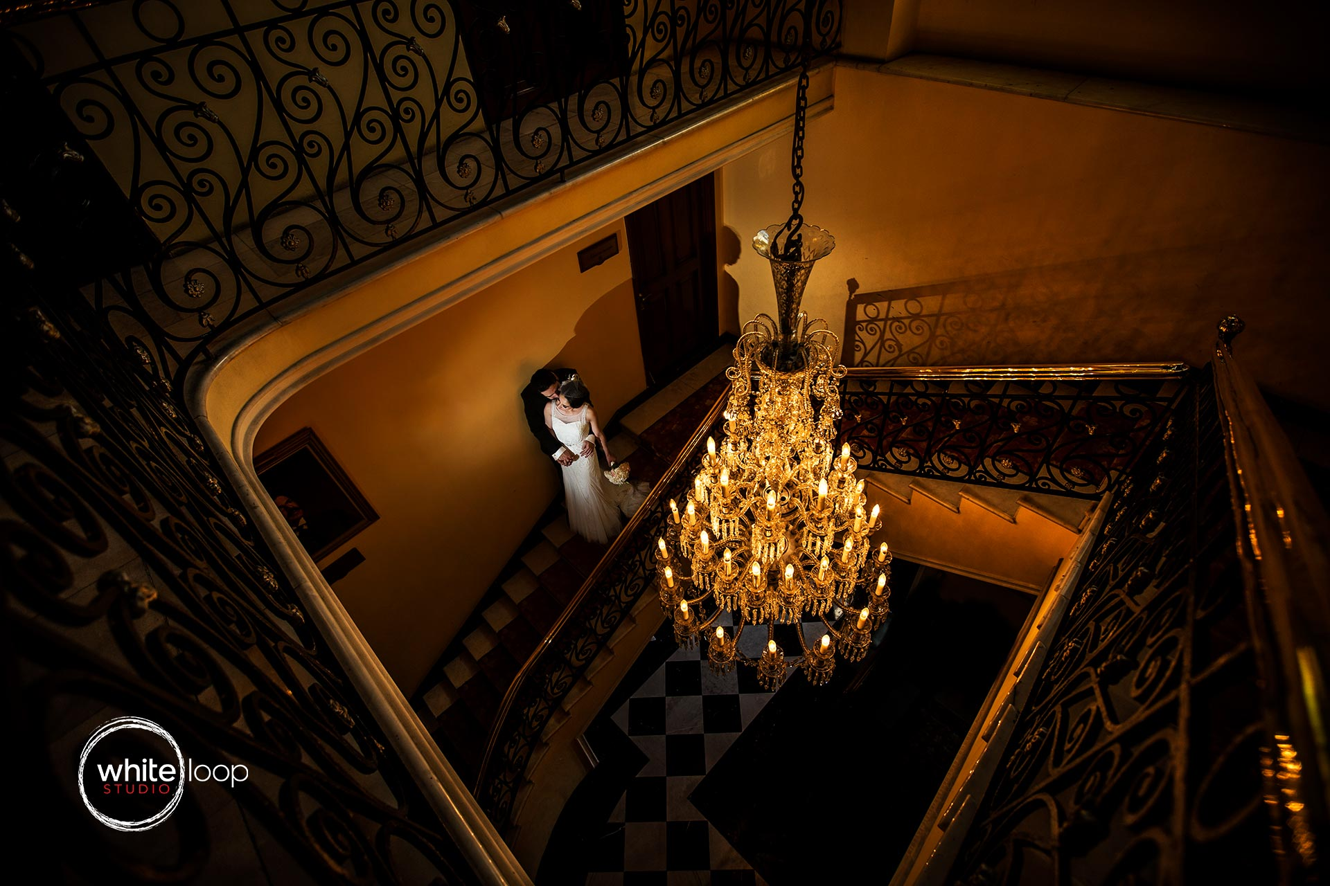 The groom and bride are holding each other in the stairs of an ancient house, illuminated by the lights of the chandelier.