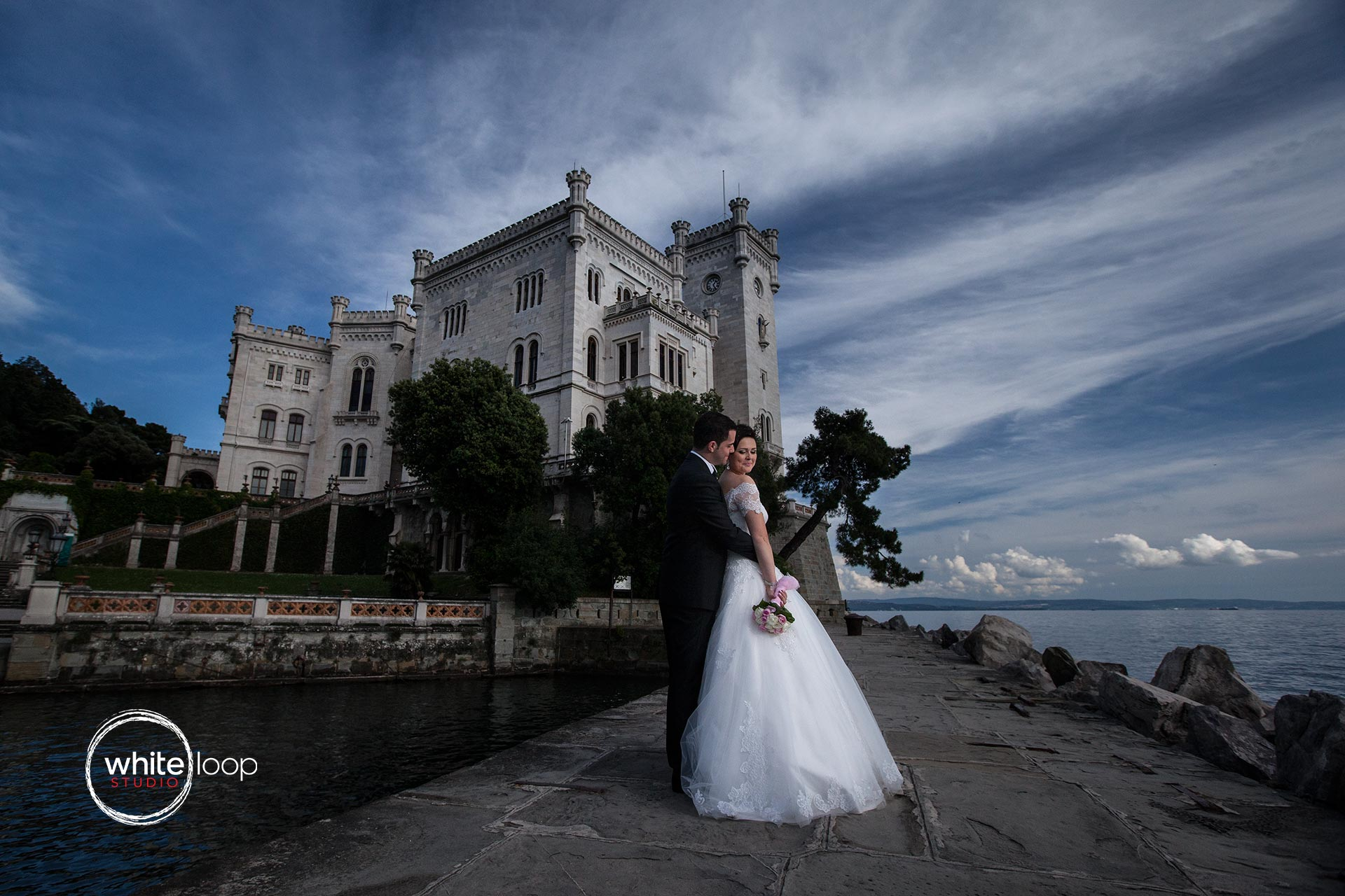 The bride and groom are holding each other on the porch of the Miramare Castle, the famous Maximilian Castle.