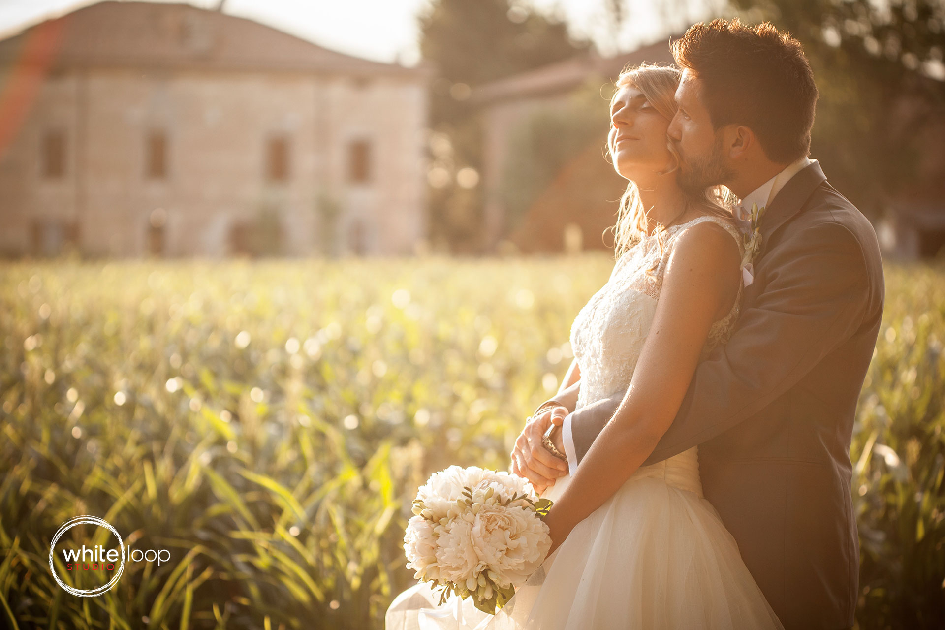 The sun is illuminating the couple that are holding each other in a very lovely way.