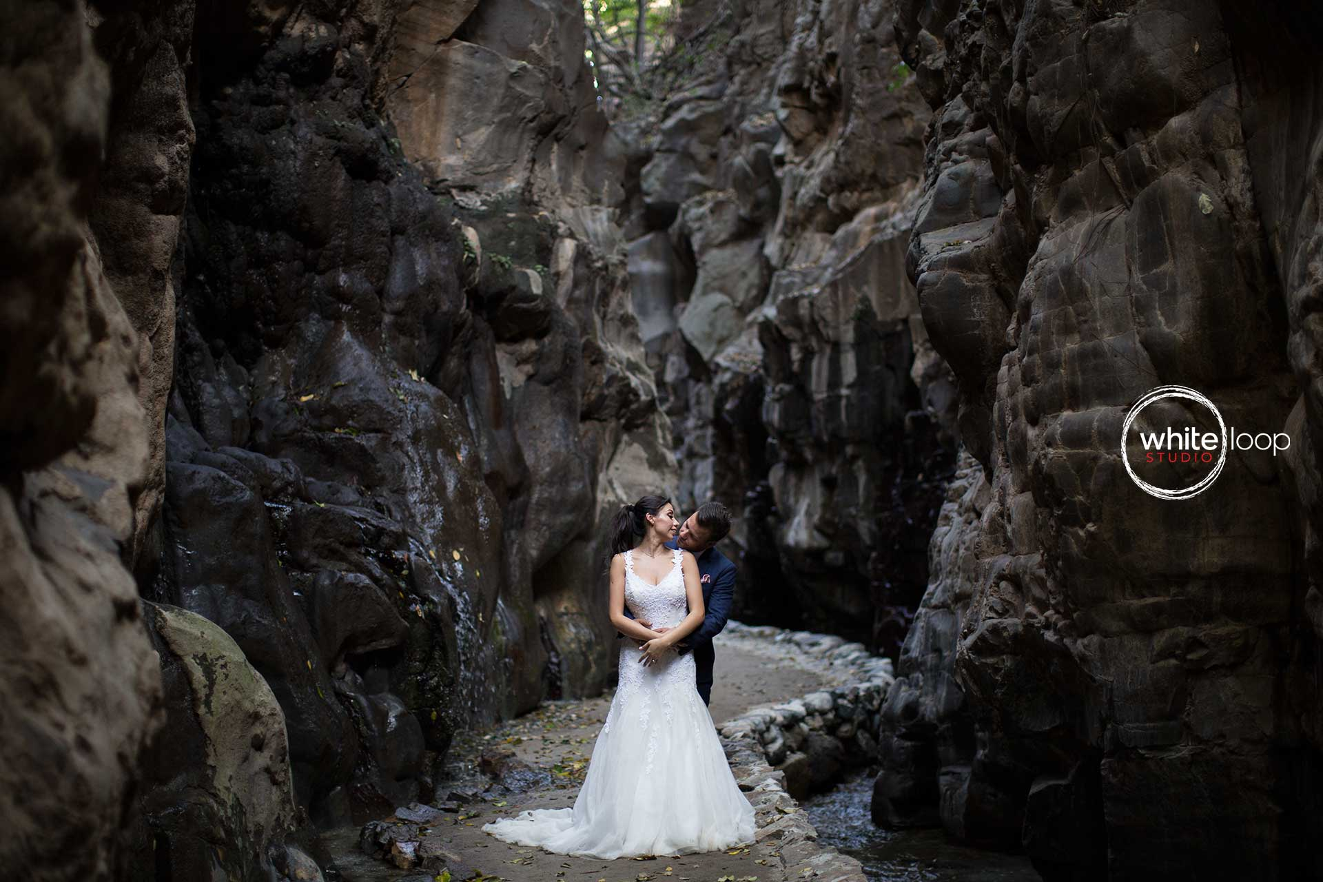 The couple is holding each other in the middle of Mexican canyon, while water is falling down and refreshing the atmosphere.