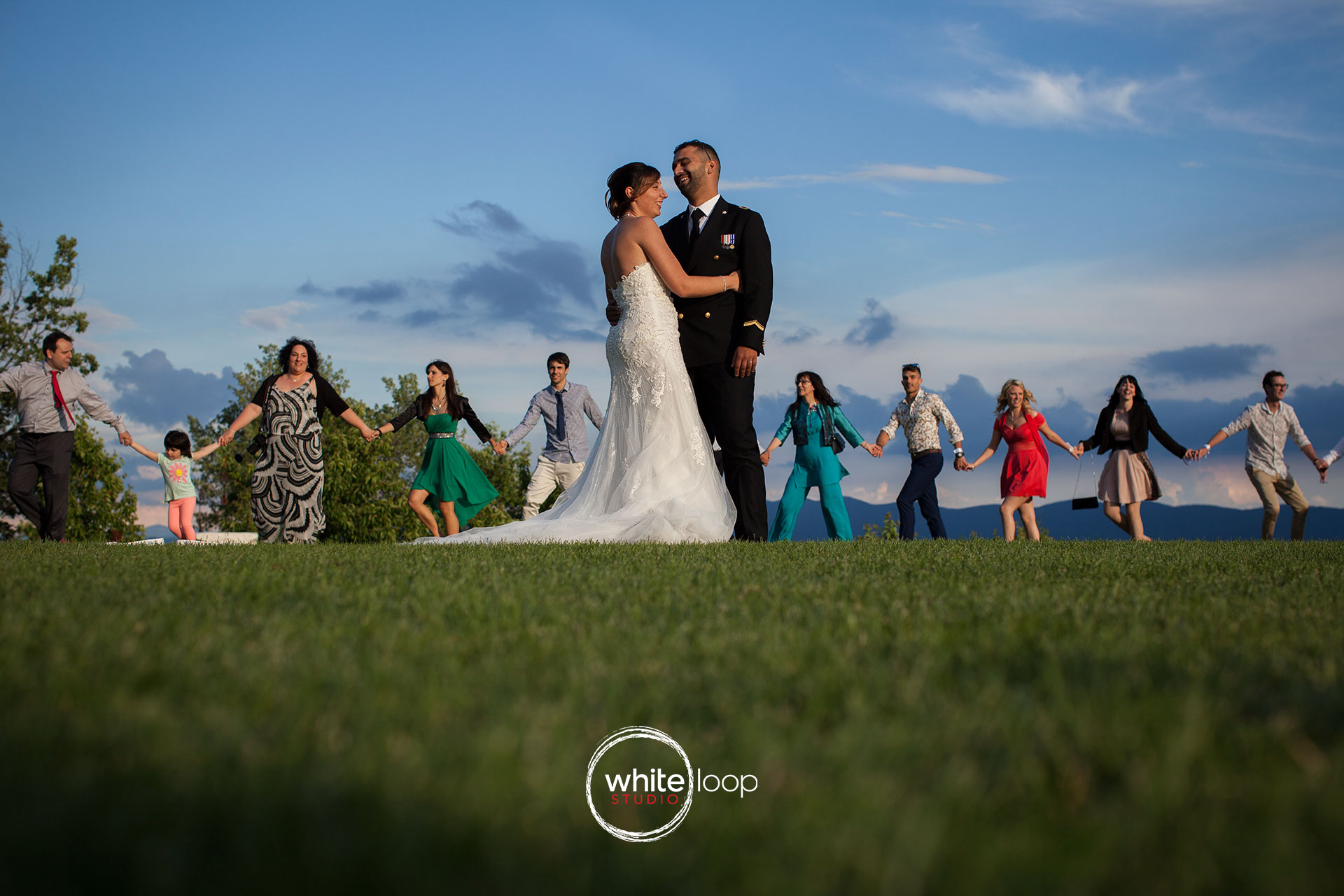 The smily couple appears to be surrounded by the guests who are dancing in circle while the sky is intensely blue and the grass perfectly cut and green.