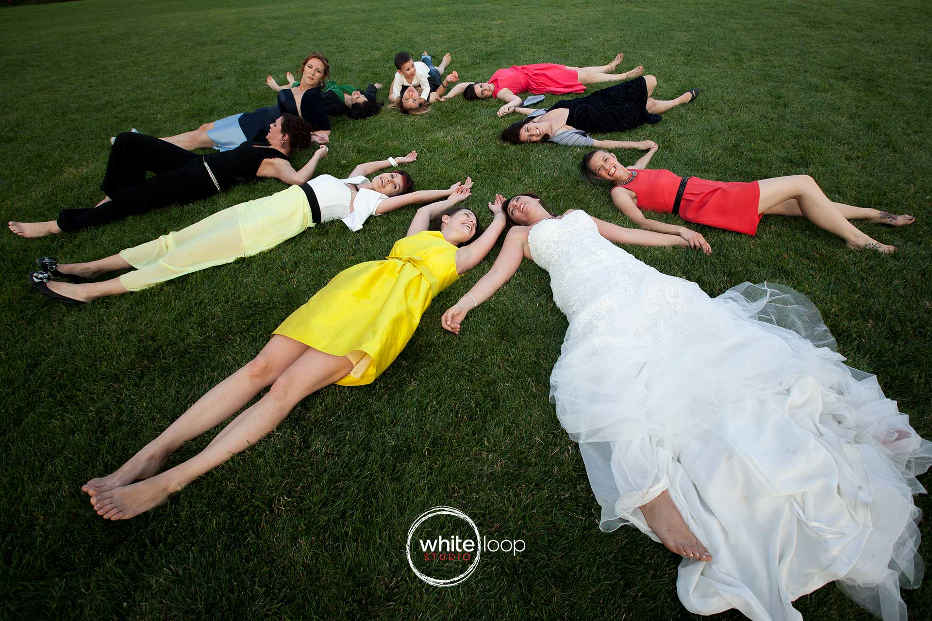 The bride is lying on the grass next to her friends, having together a moment of real relax and peace.