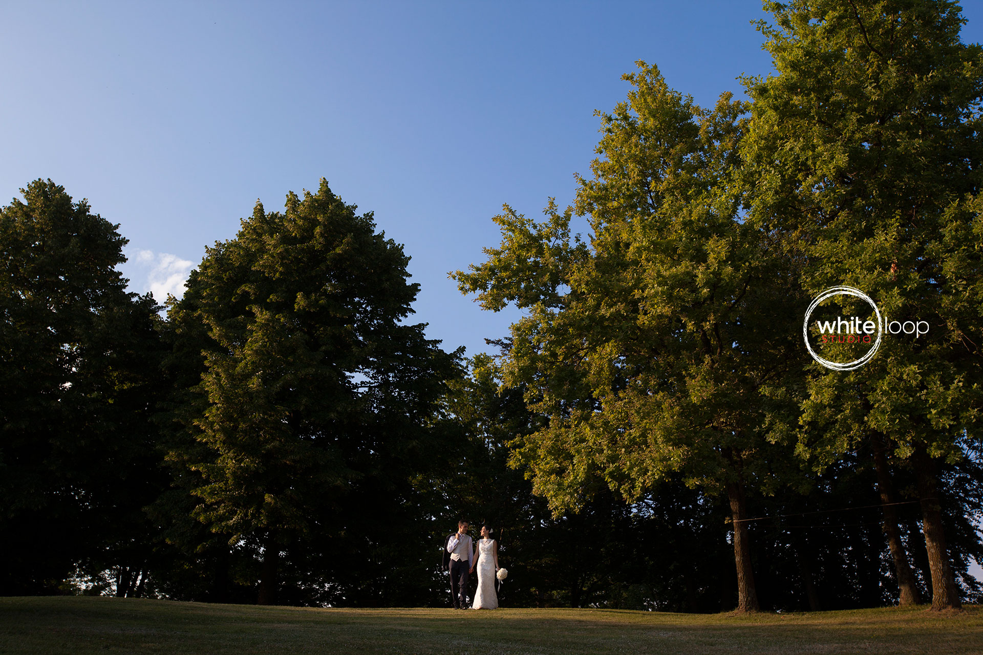 The bride and groom are holding their hands and looking each other in the middle of a Northern Italy wood