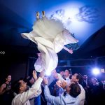 Some gentleman's at the party launch the bride in the air, celebrating the engagement between her and the groom.
