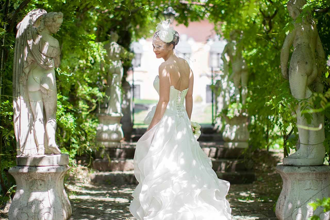 The bride walks in the historical park of the castle, while watching the camera, around of some beautiful classical statues and trees.