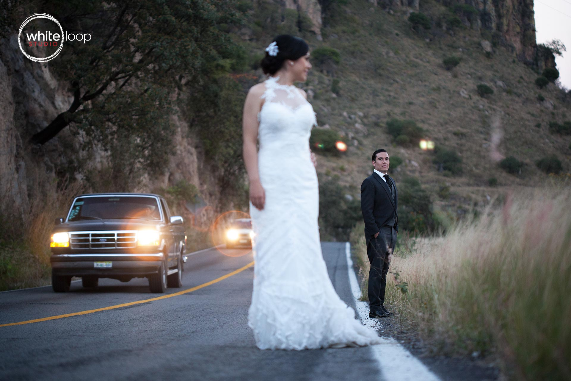 In the middle of the highway the bride and groom are looking each other smiling and escaping for a little moment.