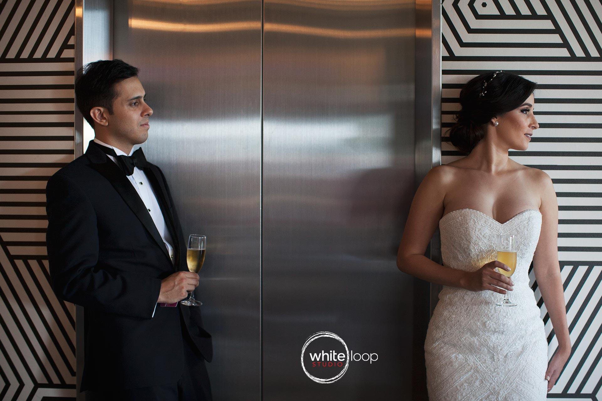 The groom is looking the beauty of the bride white they drink to celebrate some white wine, in the aisle, outside the elevator.