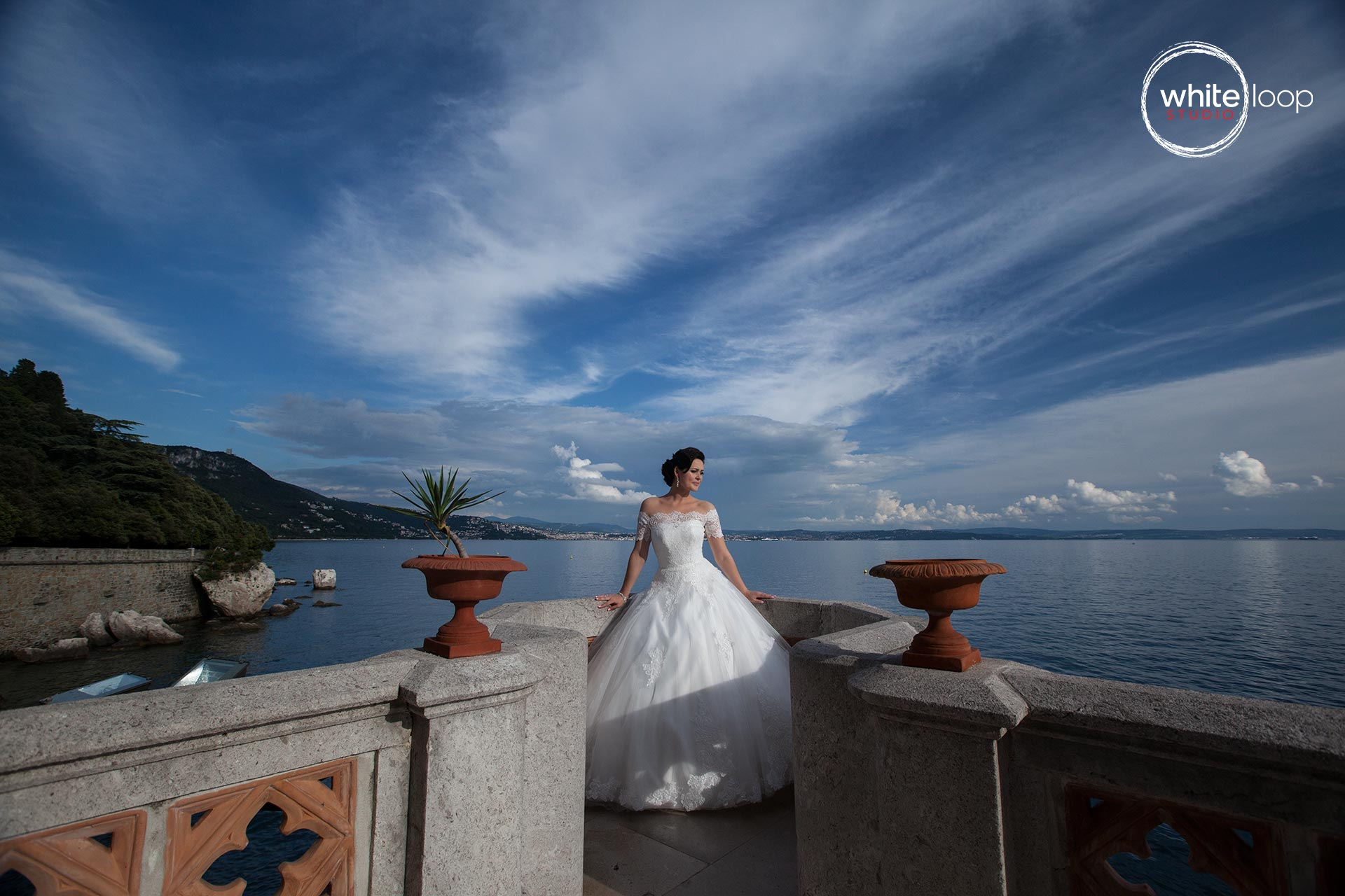 The bride in a dock and in the back she has a open sky and the blue beautiful sea of Triest.