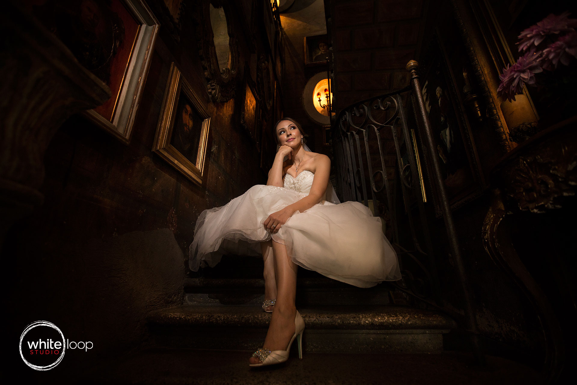 The bride is captured on the stairs, with poor light projecting the beauty of her in the wedding dress.
